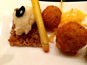 A rice/seed cracker with cheese, a cylinder, and ham croquettes