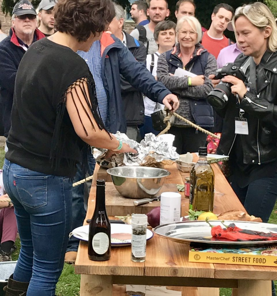 Genevieve Taylor showing how to cook mussels over fire Abergavenny Food Festival